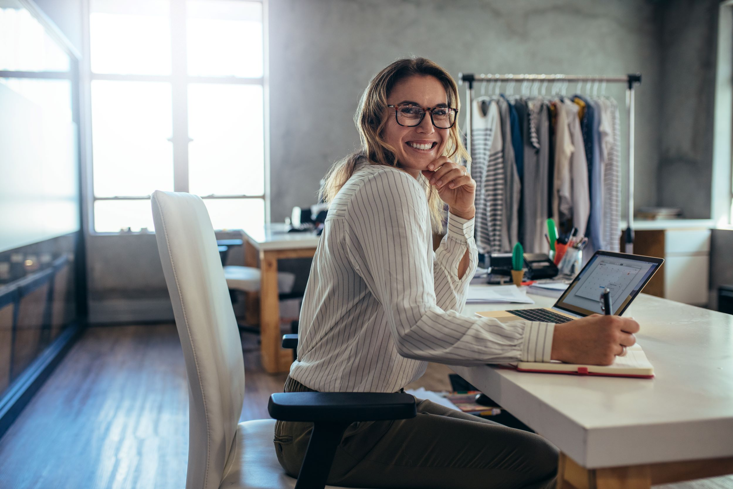 An ecommerce entrepreneur sits in front of her desk and a rack of apparel