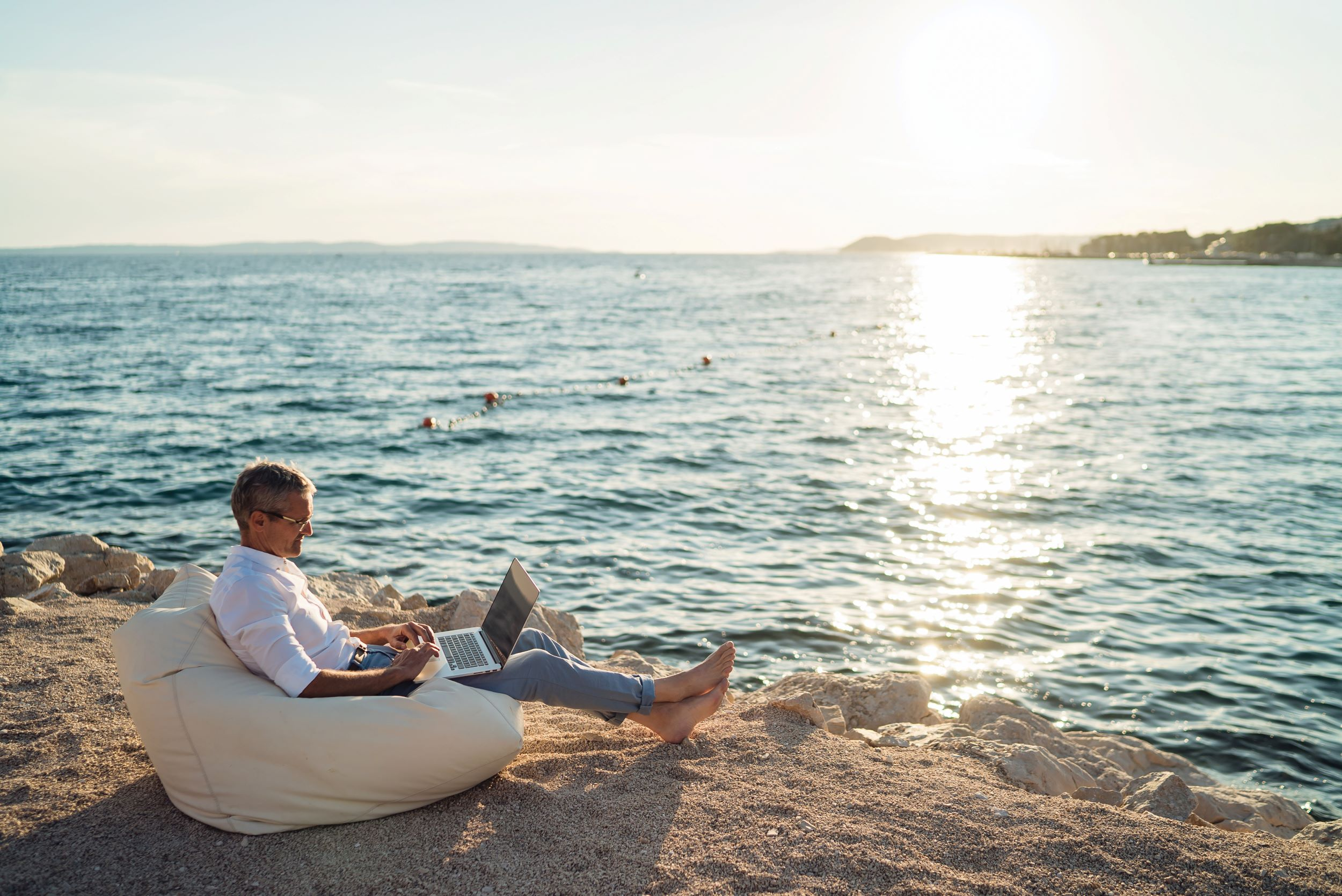 An ecommerce founder sits on a beach after successfully exiting his business