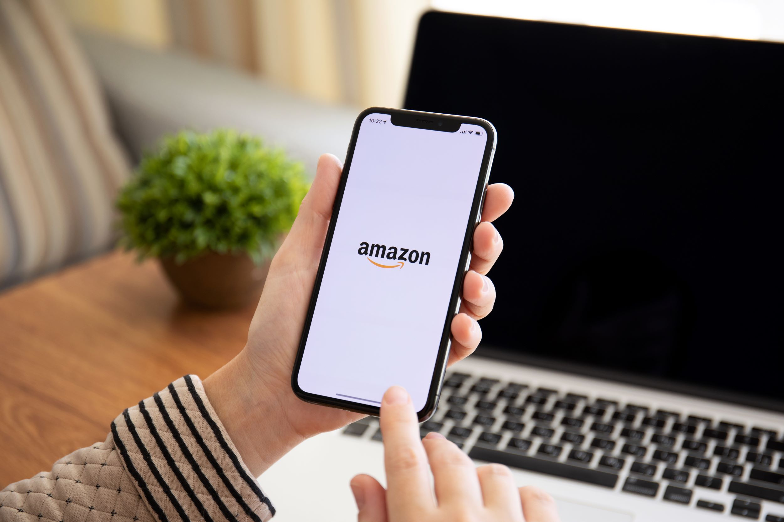 A woman holds up a phone with an Amazon logo