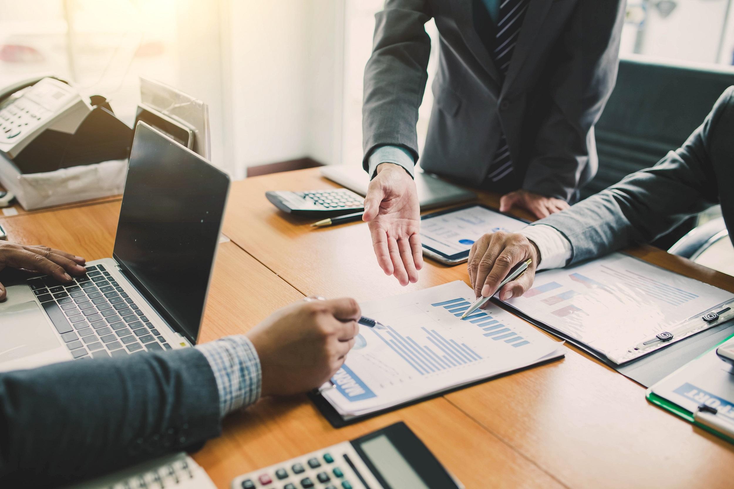 Three men analyze a revenue chart on paper