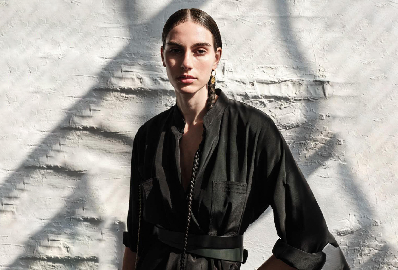 model with long hair wearing a black dress by fashion brand caravana in greece mykonos