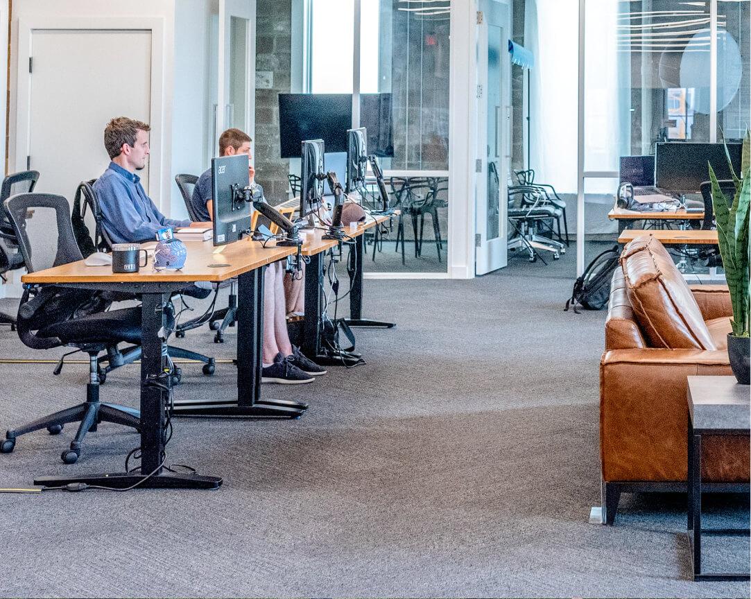 Open Space Büro mit Schreibtischen auf der Linken Seite. Zwei von drei Plätzen sind mit zwei jungen Leuten besetzt, die auf den Computer schauen. Hinten im Bild sieht man den durch Glas abgetrennten Meetingraum.