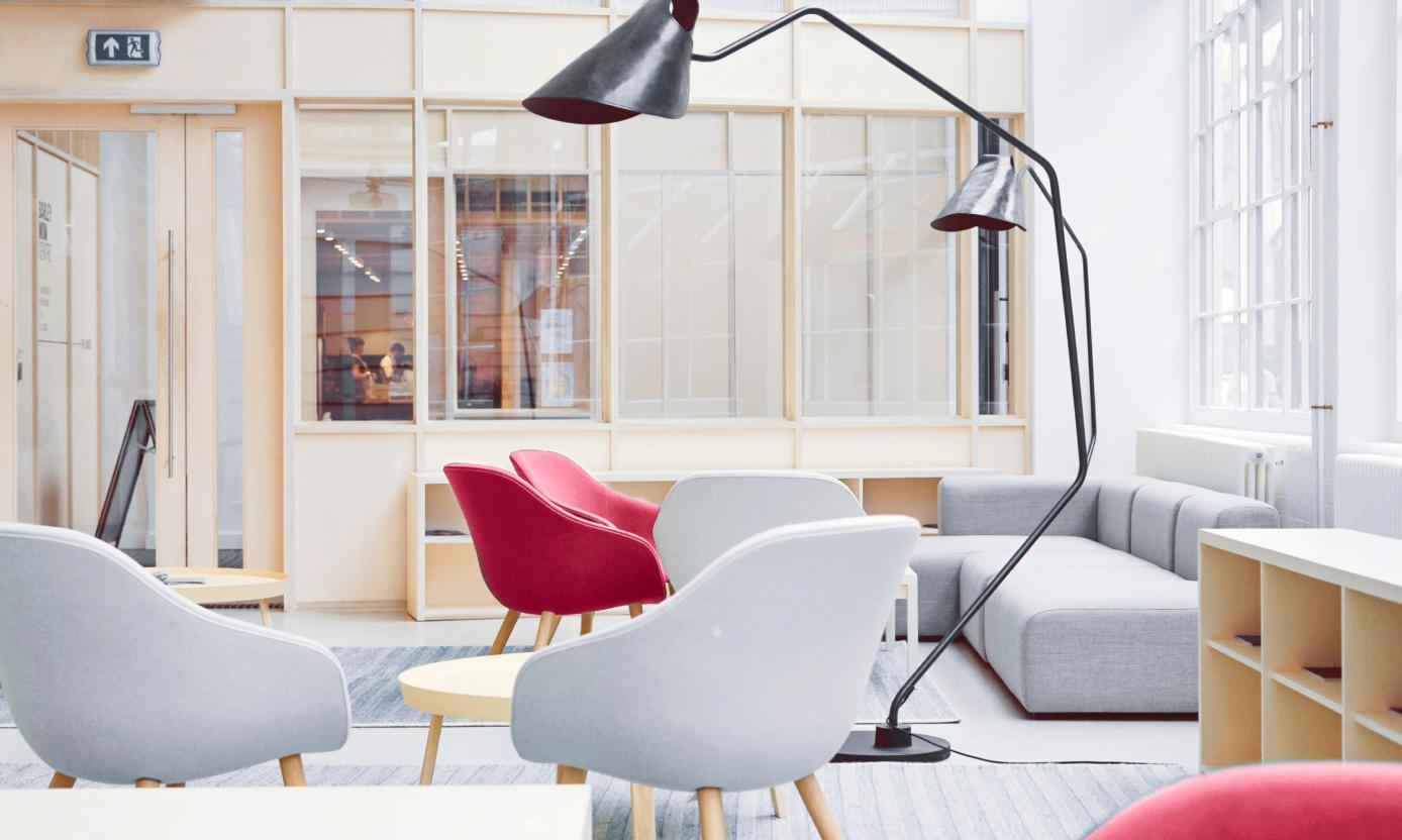 Abbildung einer Lounge im Büro mit verschiedenen Sitzmöglichkeiten aus Sesseln und Sofas. Der Raum hat viele Fenster und schöne Leselampen.