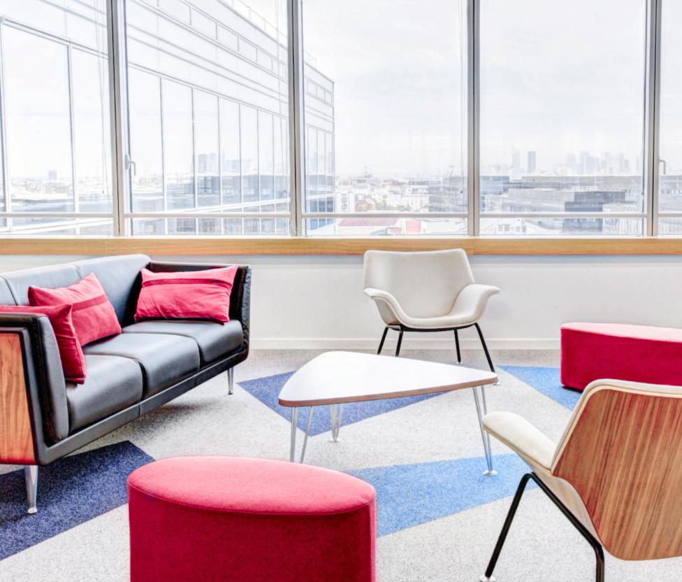Abbildung einer Lounge im Büro mit verschiedenen Sitzmöglichkeiten aus Sesseln und Sofas. Mit Blick durch ein großes Fenser auf die Stadt.