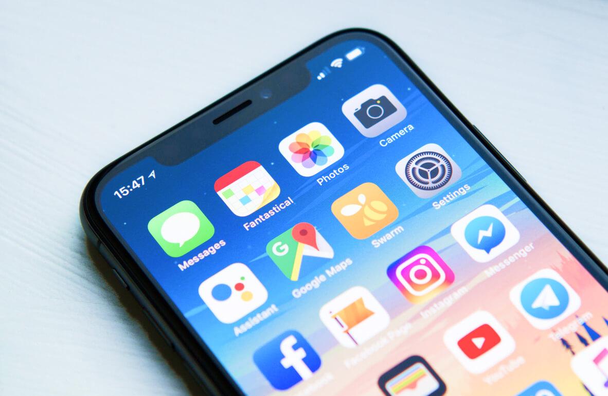 Abbildung eines schwarzen iPhone vom Startbildschirm. Auf einem blauen Hintergrund.