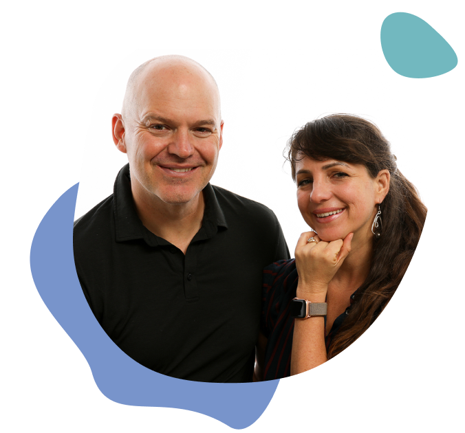 A white man and a woman stand next to each other, smiling. They are Figs and Teale, relationship experts and romantic partners.