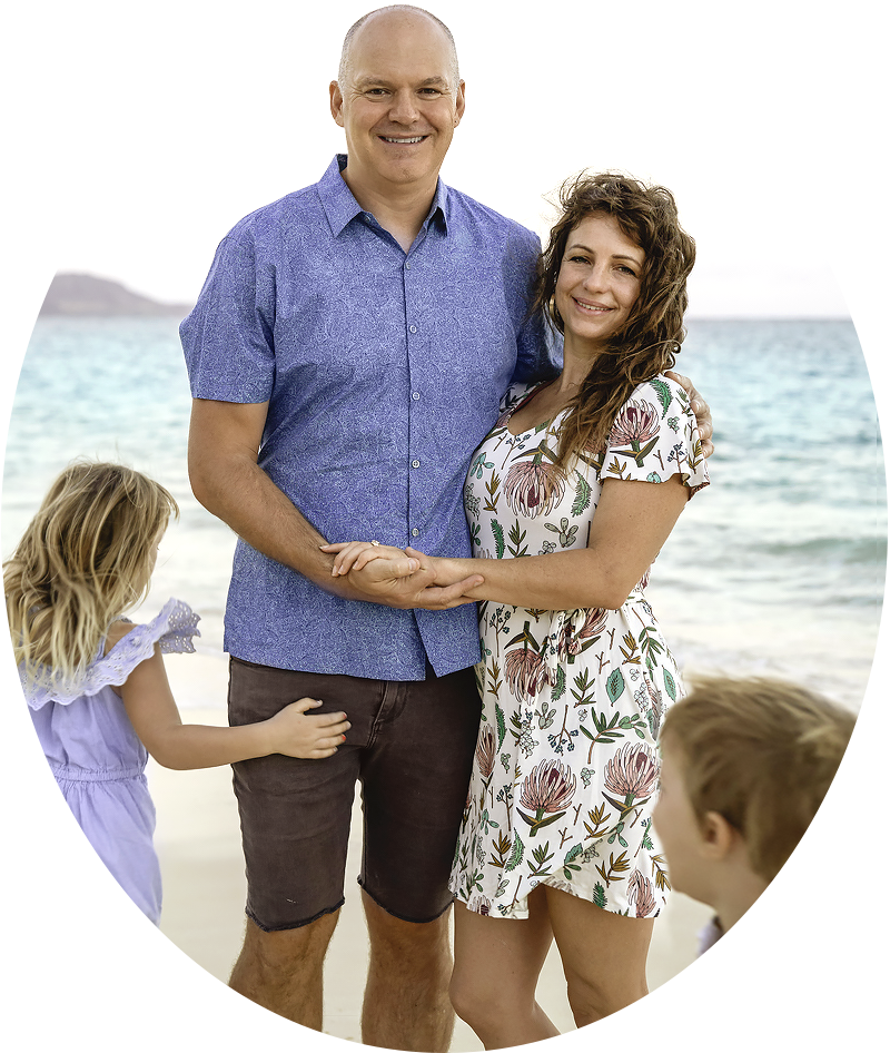 Figs, Teale smile together at the beach as their son and daughter play around them.