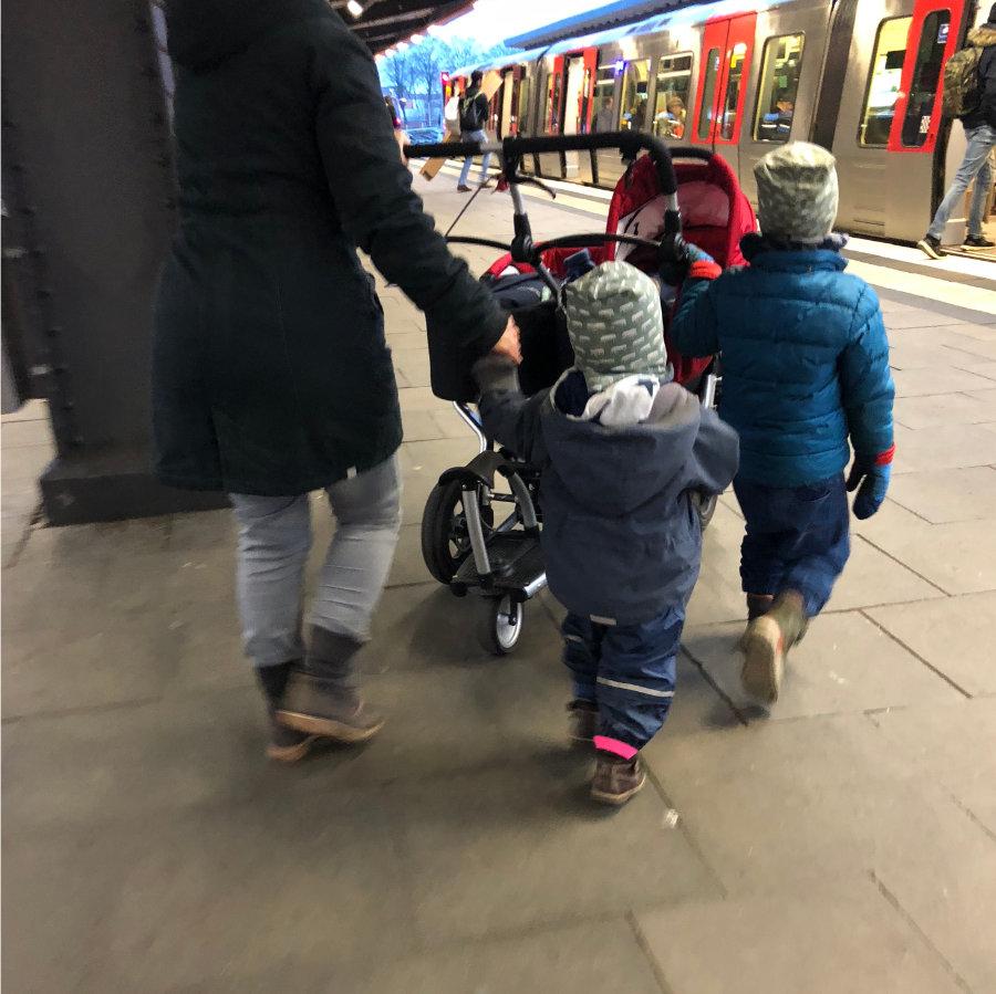 Familie mit Kleinkindern geht auf Metro zu