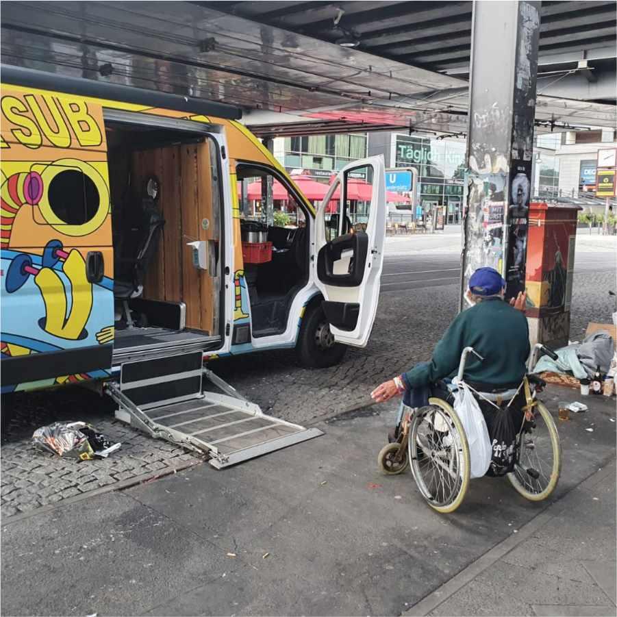 Ein Obdachloser Mensch im Rollstihl rollt  auf den geöffneten Karunabus zu