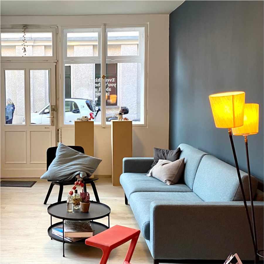 Foto Büro mit einem blauen Sofa und bunten Hockern