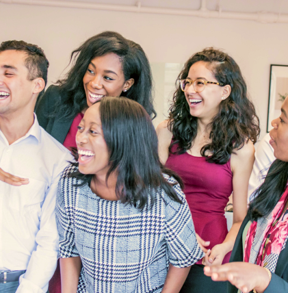 A group of young men and women in business attire laughing at something out of frame