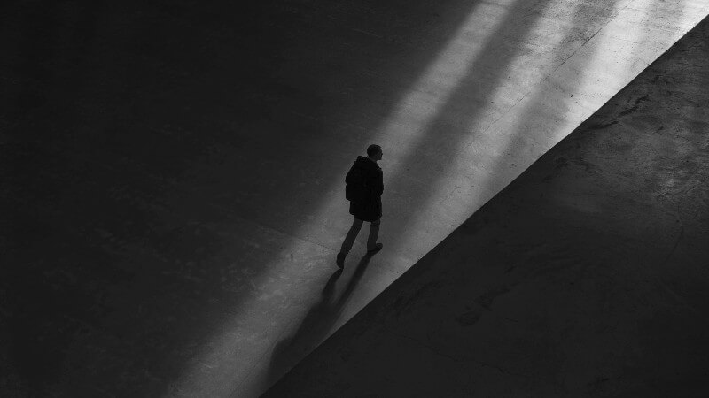 Man walking in dark room with only a small ray of light