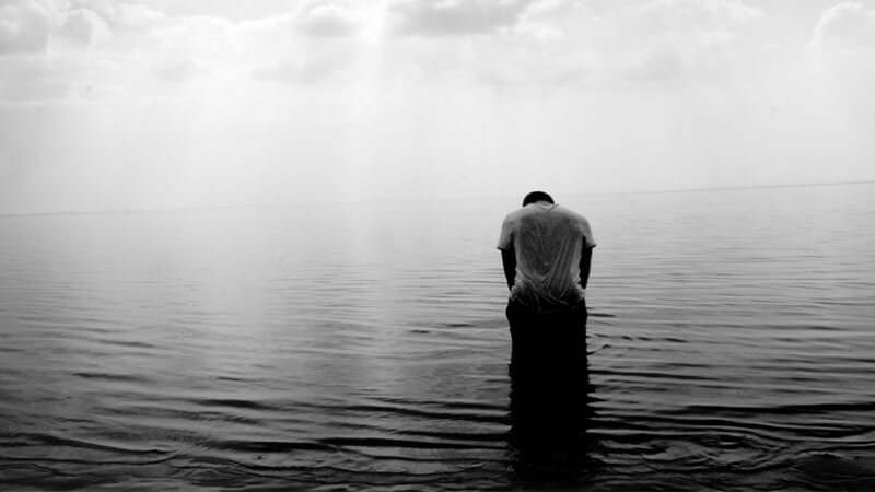 black and white photo of man standing in lake