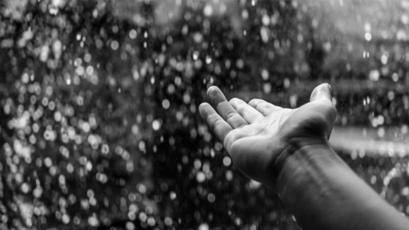 Hand reaching out into the rain