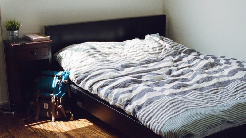 A bedroom with backpack next to the bed