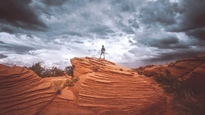 Woman standing firm on large rock