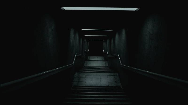 Staircase Going Down Into a Dark Place with Dim Lights