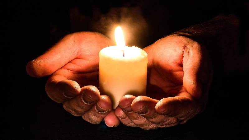 Hands Holding a Bright Candle in the Dary
