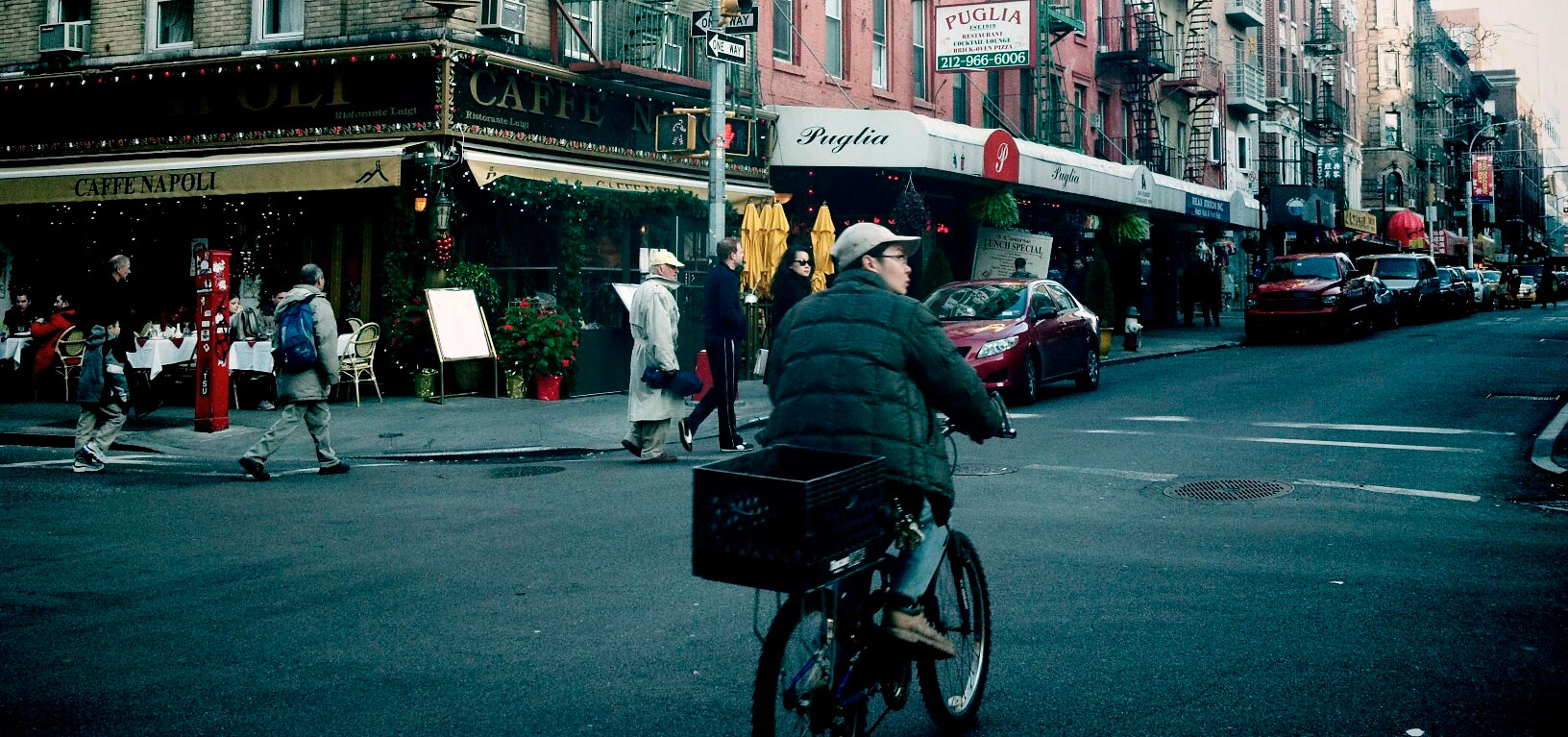 street scene of NYC with bicycle delivery person in foreground