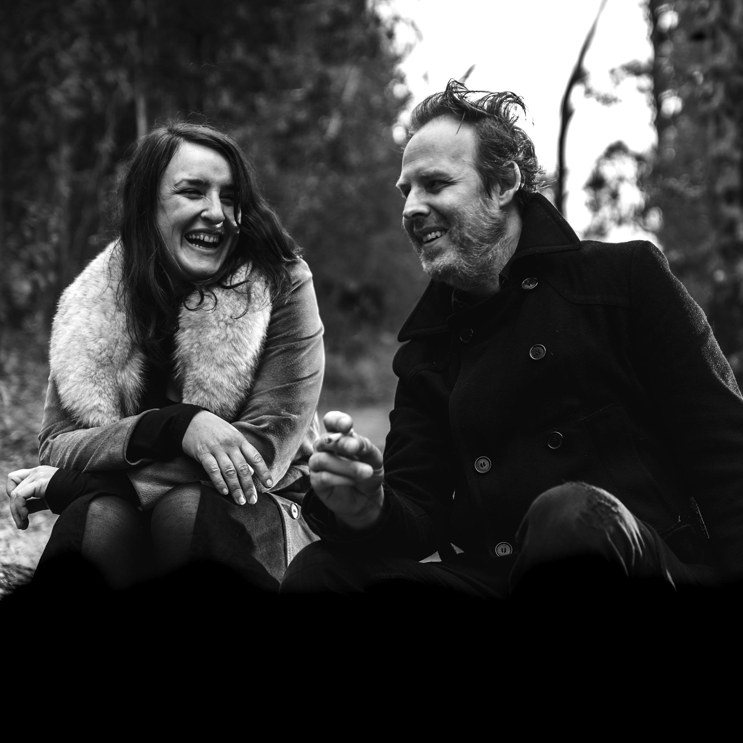 Black and white photo of Katie Scott sitting next to Brett Poliness laughing.