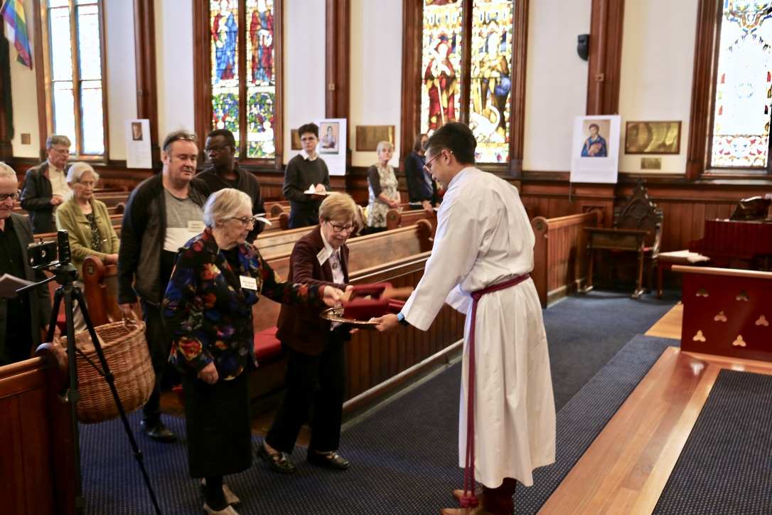 robed individual accepting offering bags from parishioners