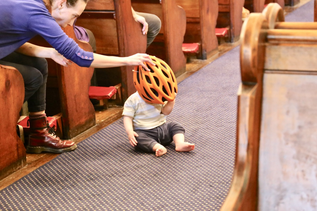 baby in aisle of church with bicycle helmet covering its face