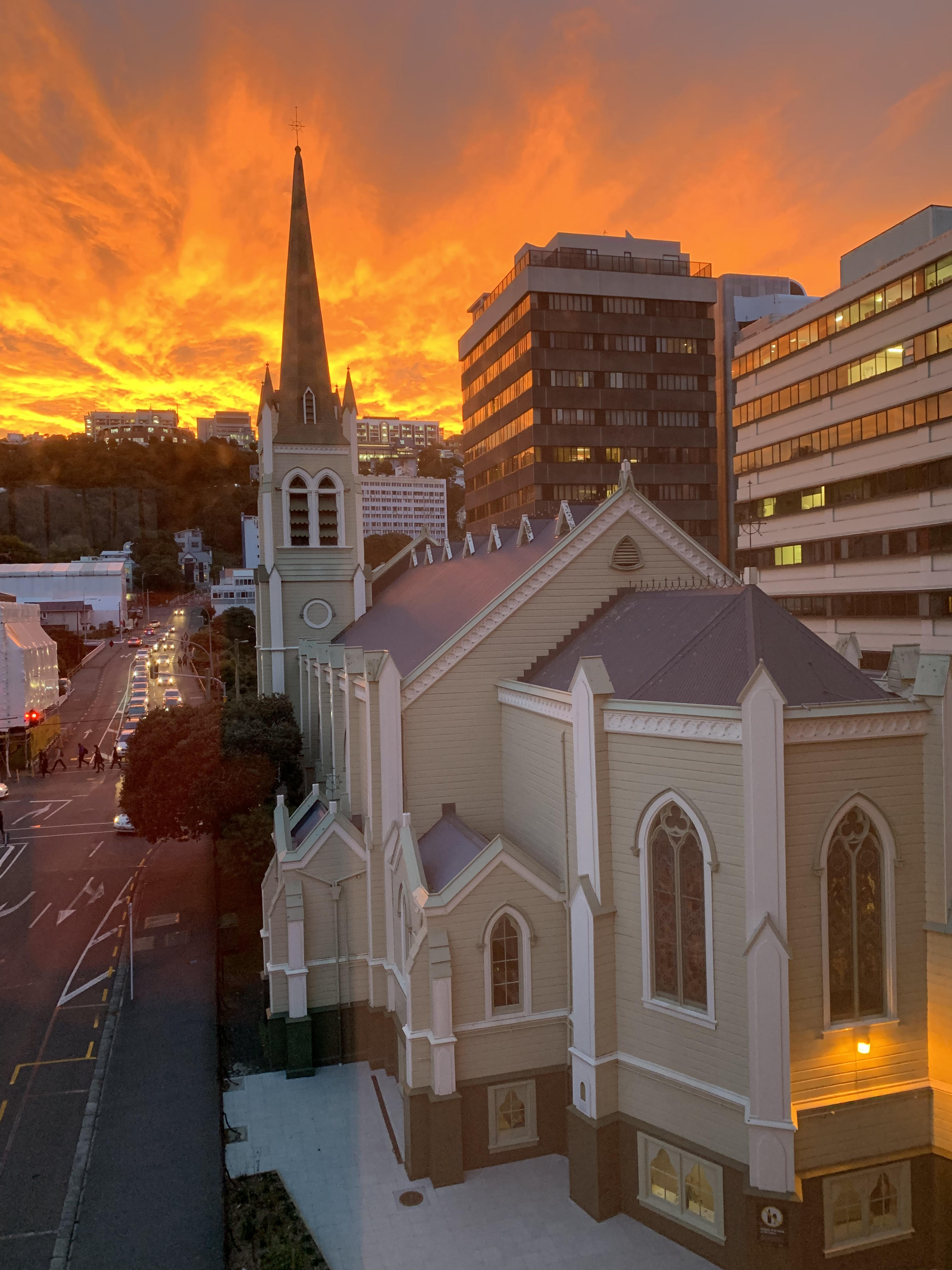 Sun sets behind church building.