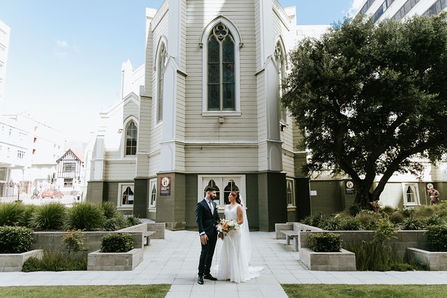 Couple in wedding dress and tuxedo stands in front of church building in garden.