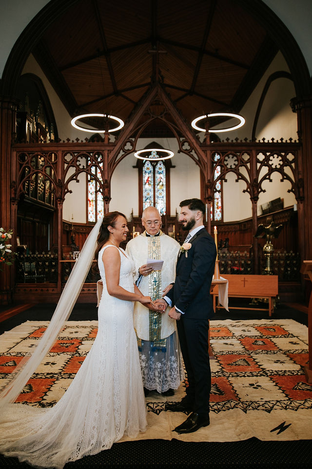 Couple stands at front of church during wedding ceremony with minister behind them.