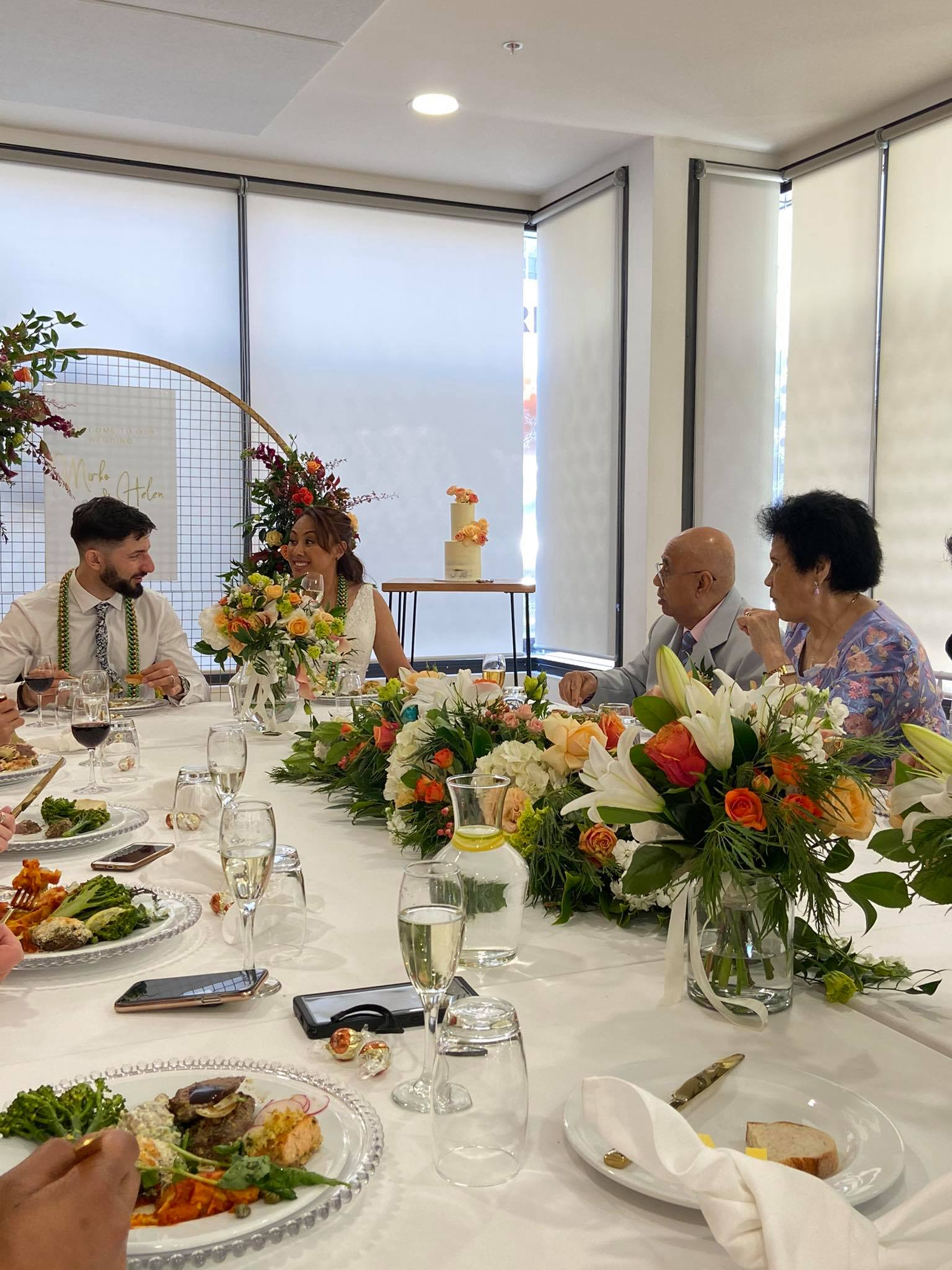 Couple sits at head of table of wedding banquet.