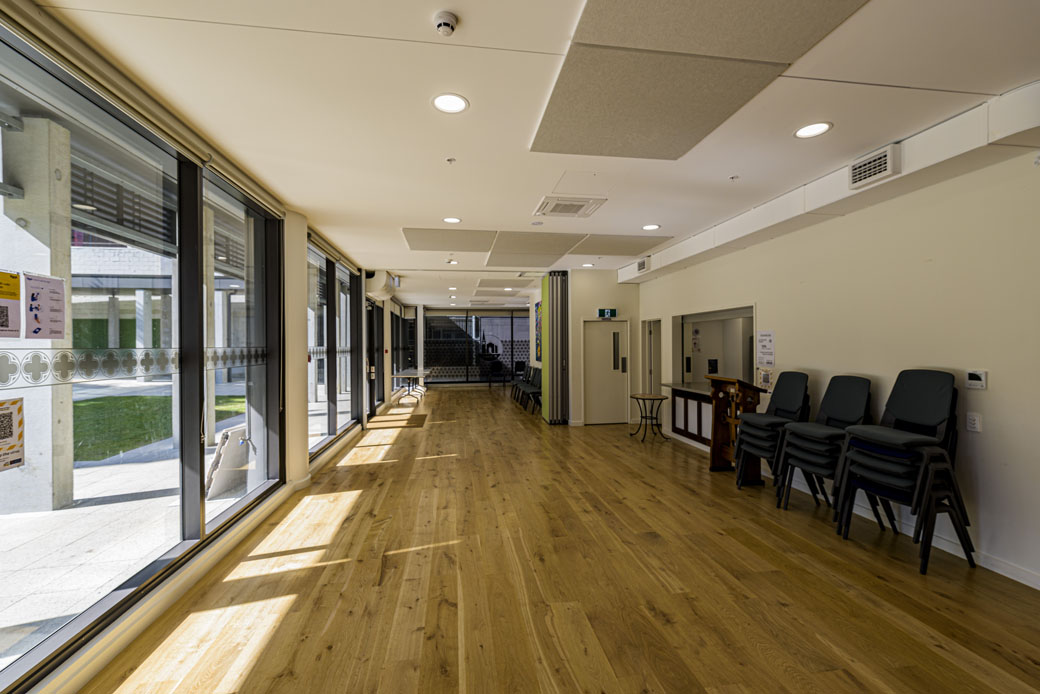 Empty room with wood floors and large windows.