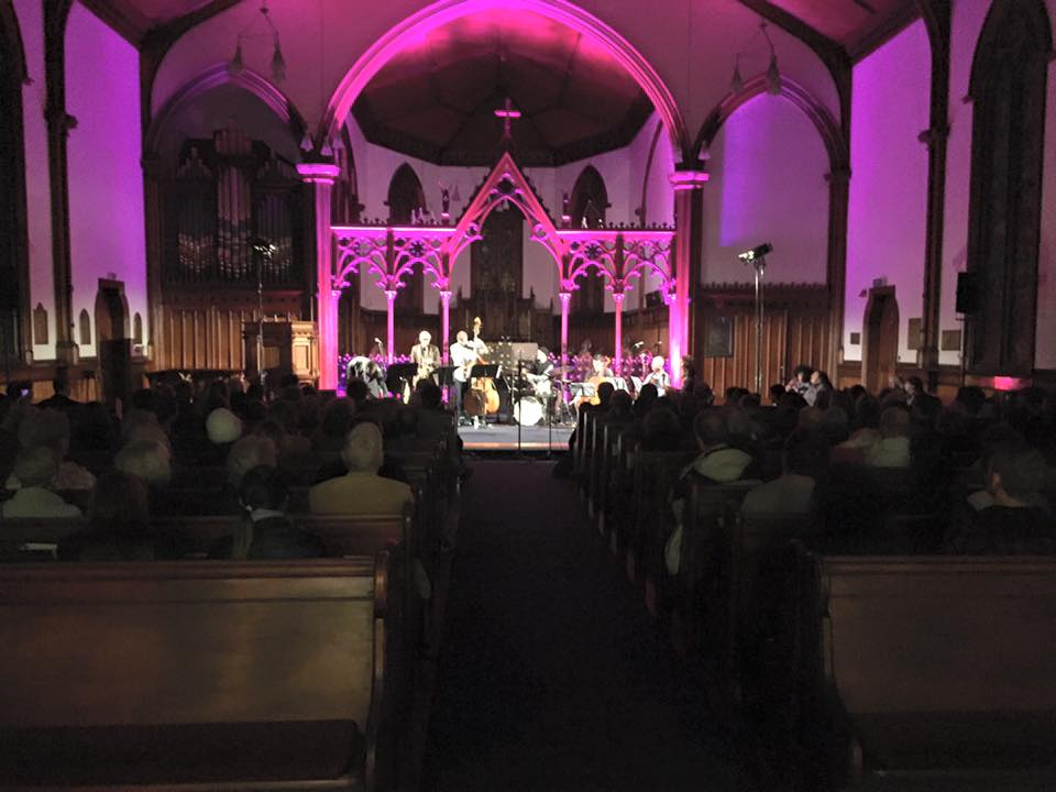 Musicians stand at front of church; church is lit with purple lights.