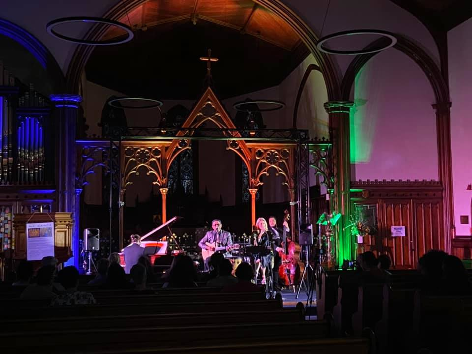 Musicians stand at front of church; church is lit with blue, green, and purple lights.