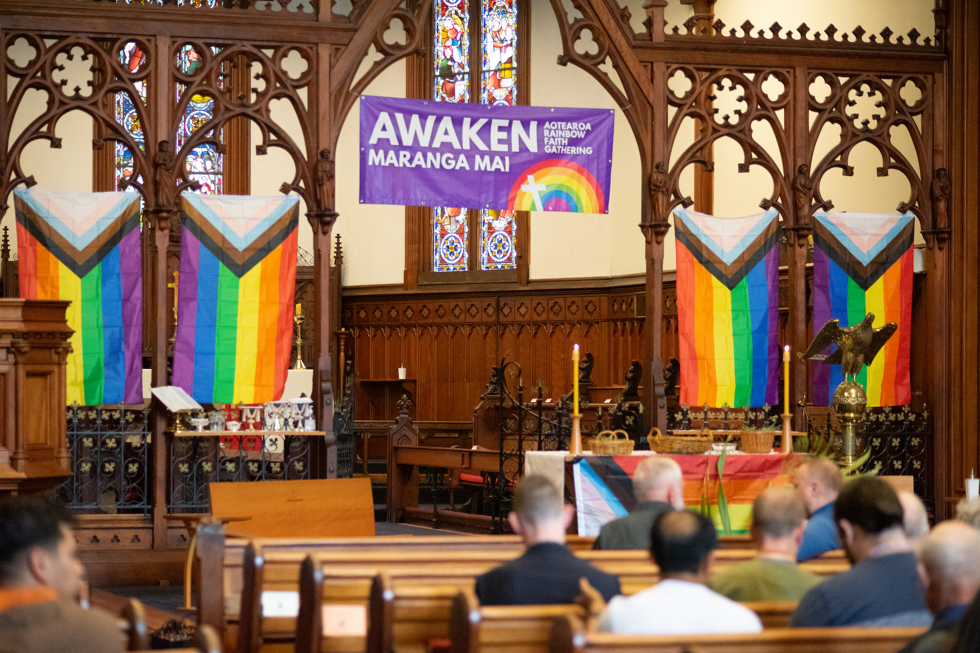 Rainbow banners hang at front of church; people sit in pews.