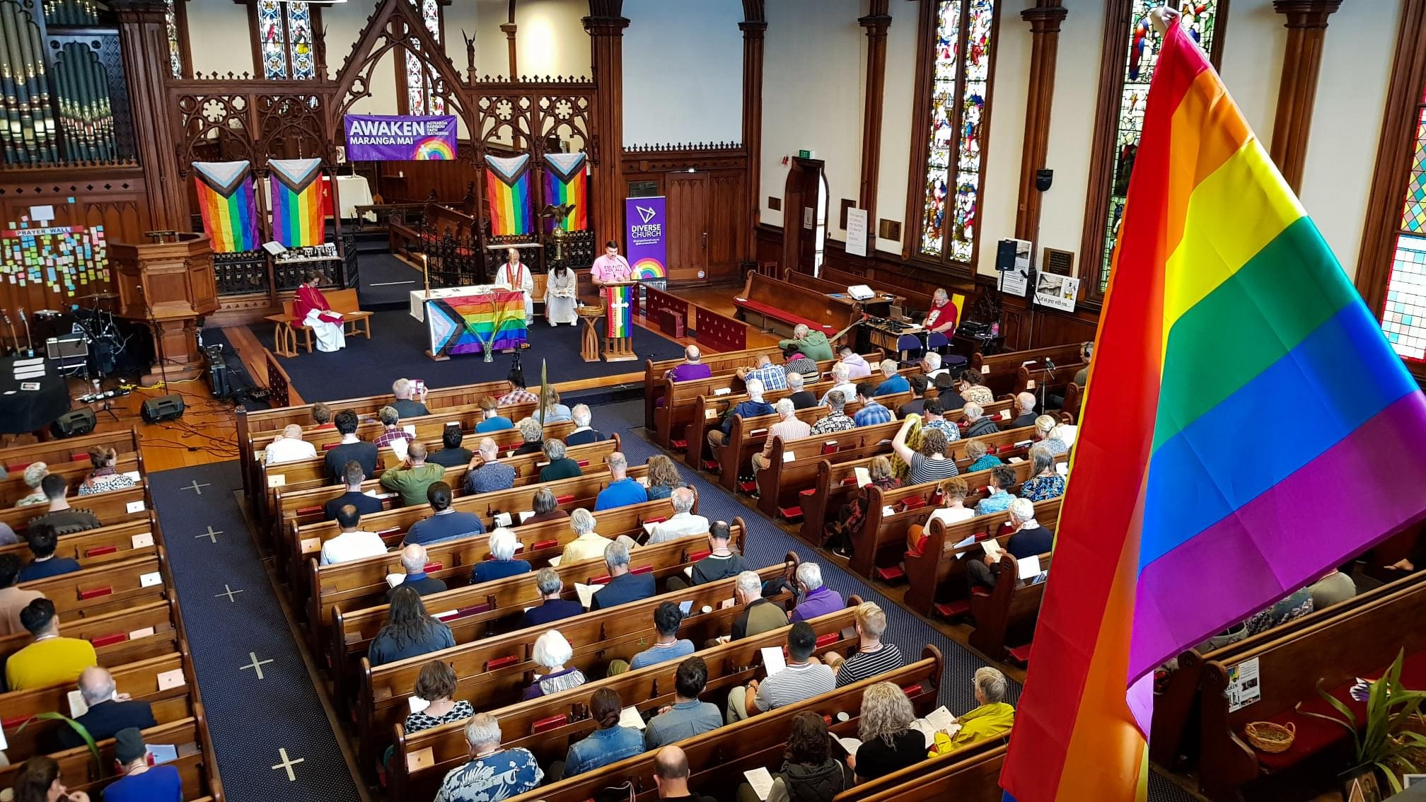 A rainbow flag is in foreground with people in pews at church.