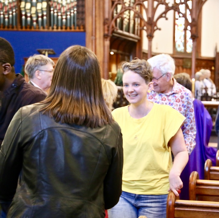 Two young women greet each other at worship service
