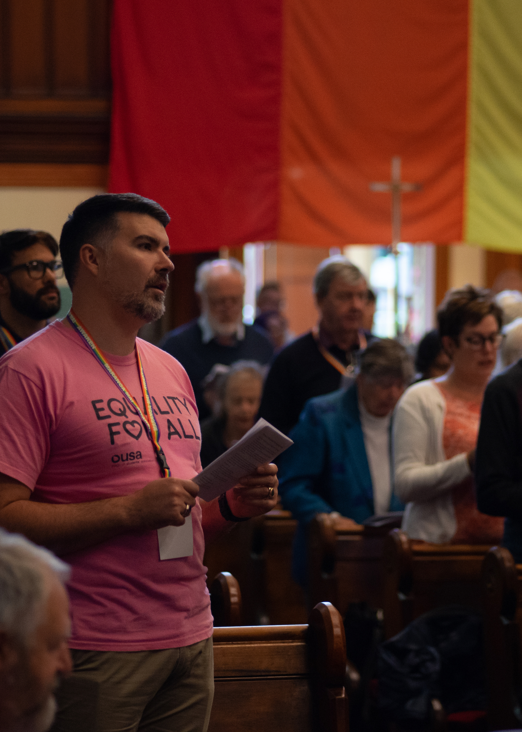Male with pink shirt that says Equality for All at worship service; large rainbow banner hangs in the background