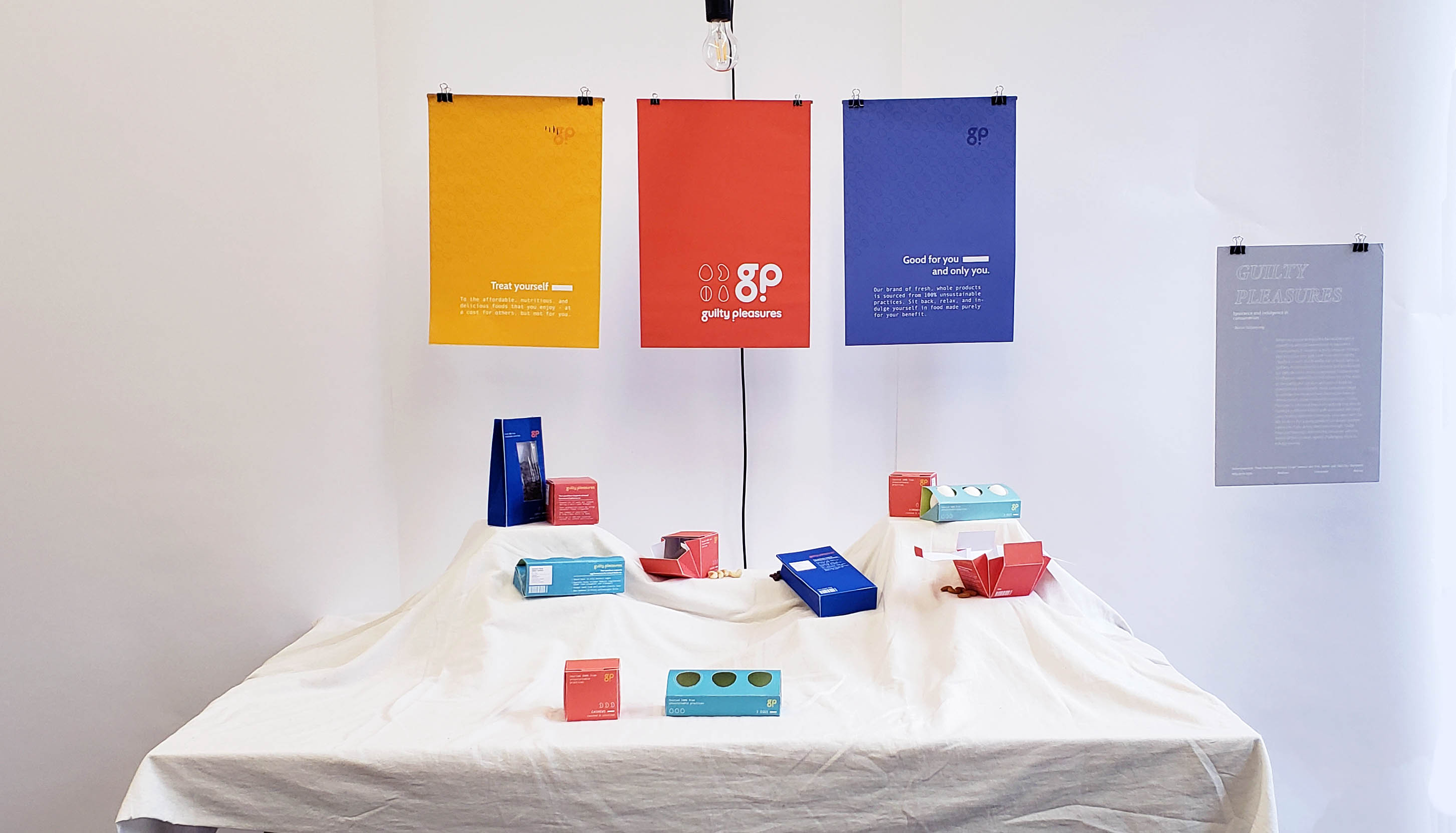 A table covered in white cloth with colourful packages displayed on top. Three banners showing the brand logo hang above.