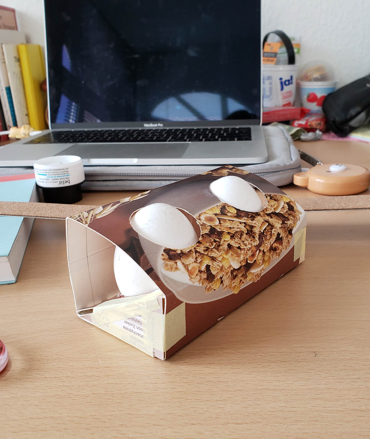 A prototype of the final egg package made out of a cereal box. The paper structure includes cutouts along the top and side which exposes the eggs to the air.