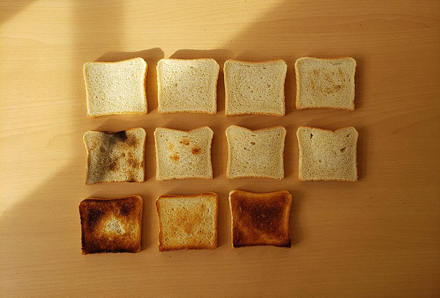 A spread of eleven slices of toast, all in a variety of cooked, uncooked, and totally burnt states.