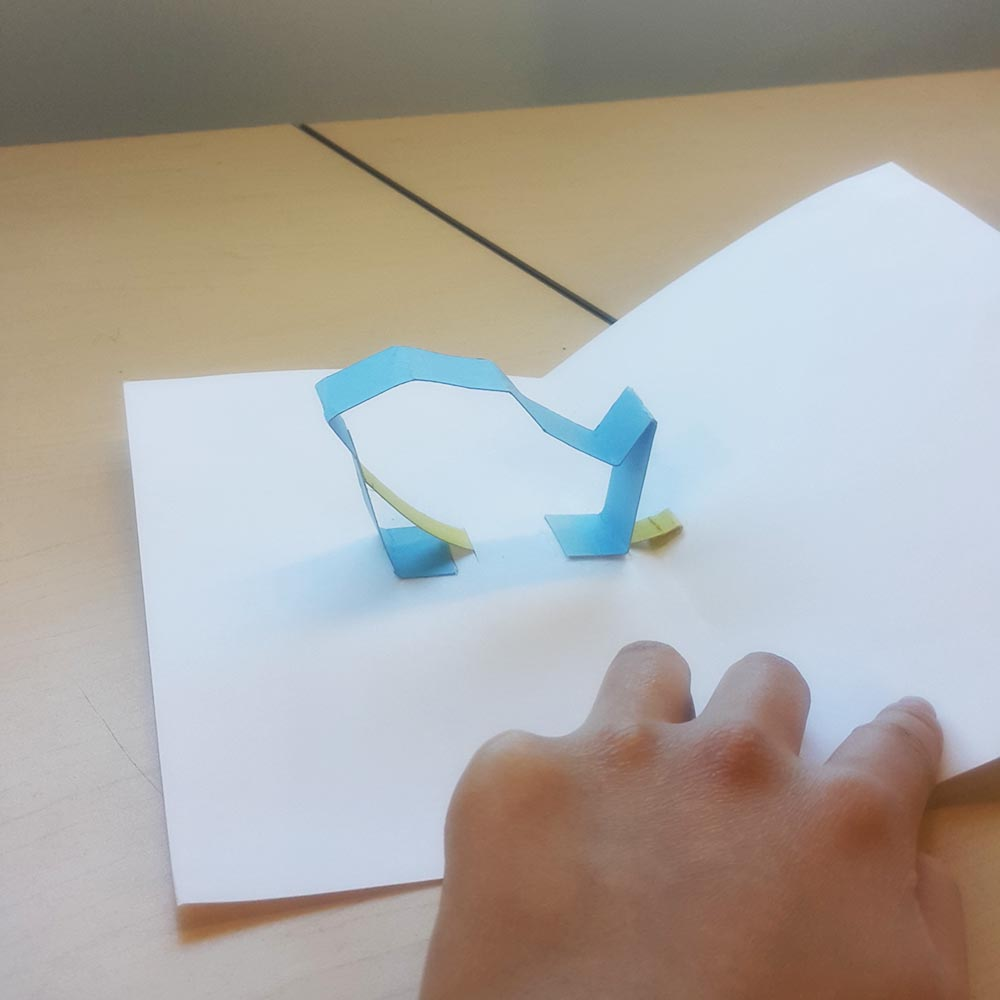 A white pop up paper card that contains a compressed piece of folded blue paper, which unfolds into the shape of a bird when the card is opened.