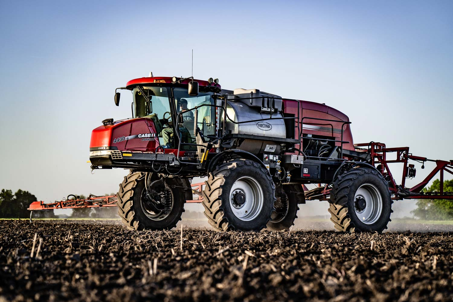 A Case IH 4430 sprayer with 650/65R38 floaters applying a pre-emerge herbicide.