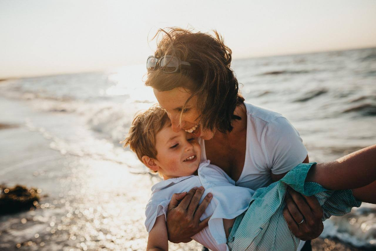 A cancer survivor enjoys quality time with her grandchild on the beach.