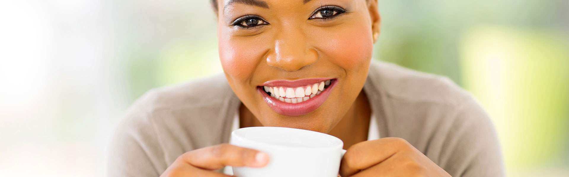 Woman smiling while enjoying a cup of coffee