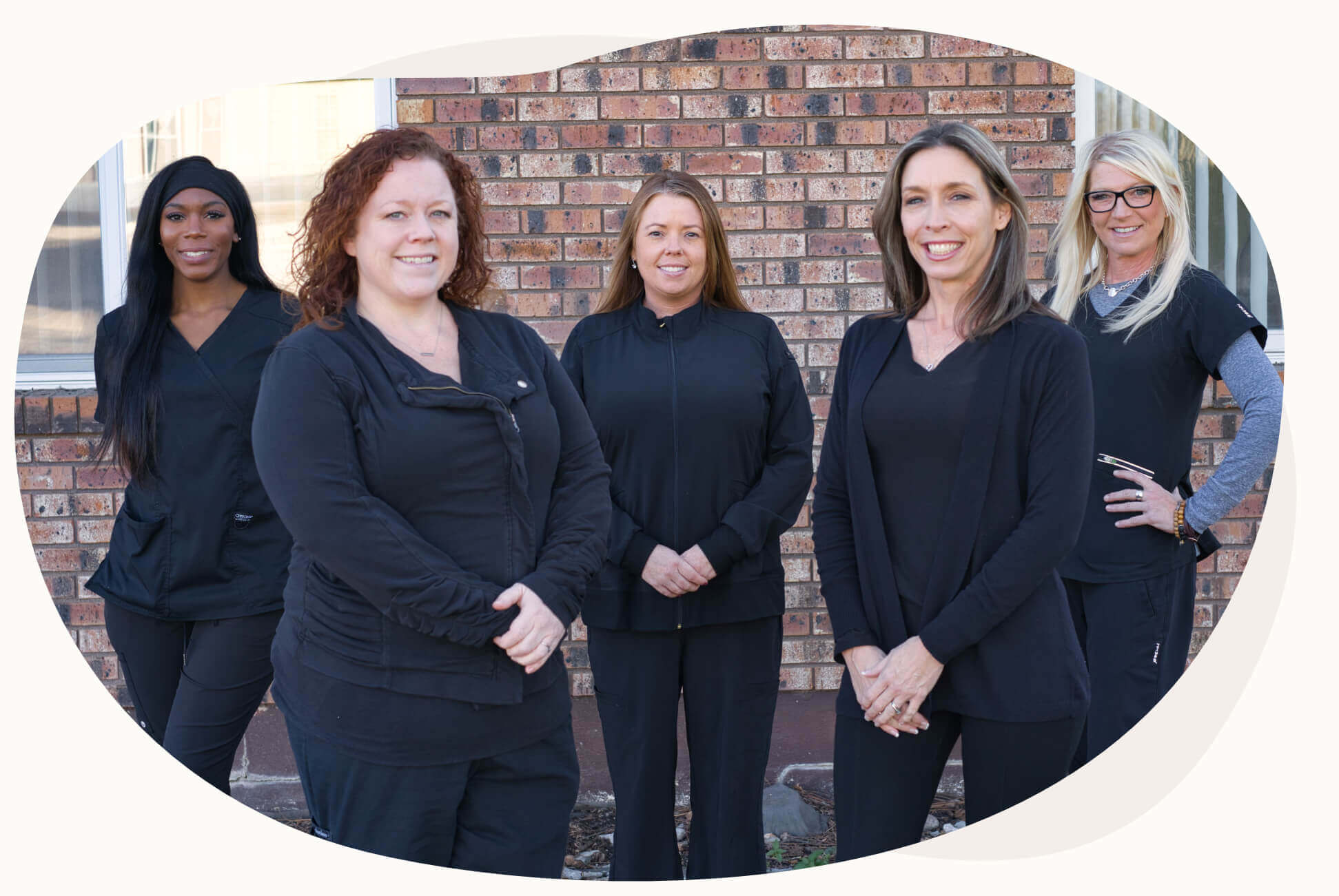 The dental team at Town & Country Dentistry smiling as a group in front of the office.