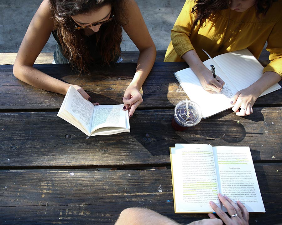 Young Adults reading and studying outside.