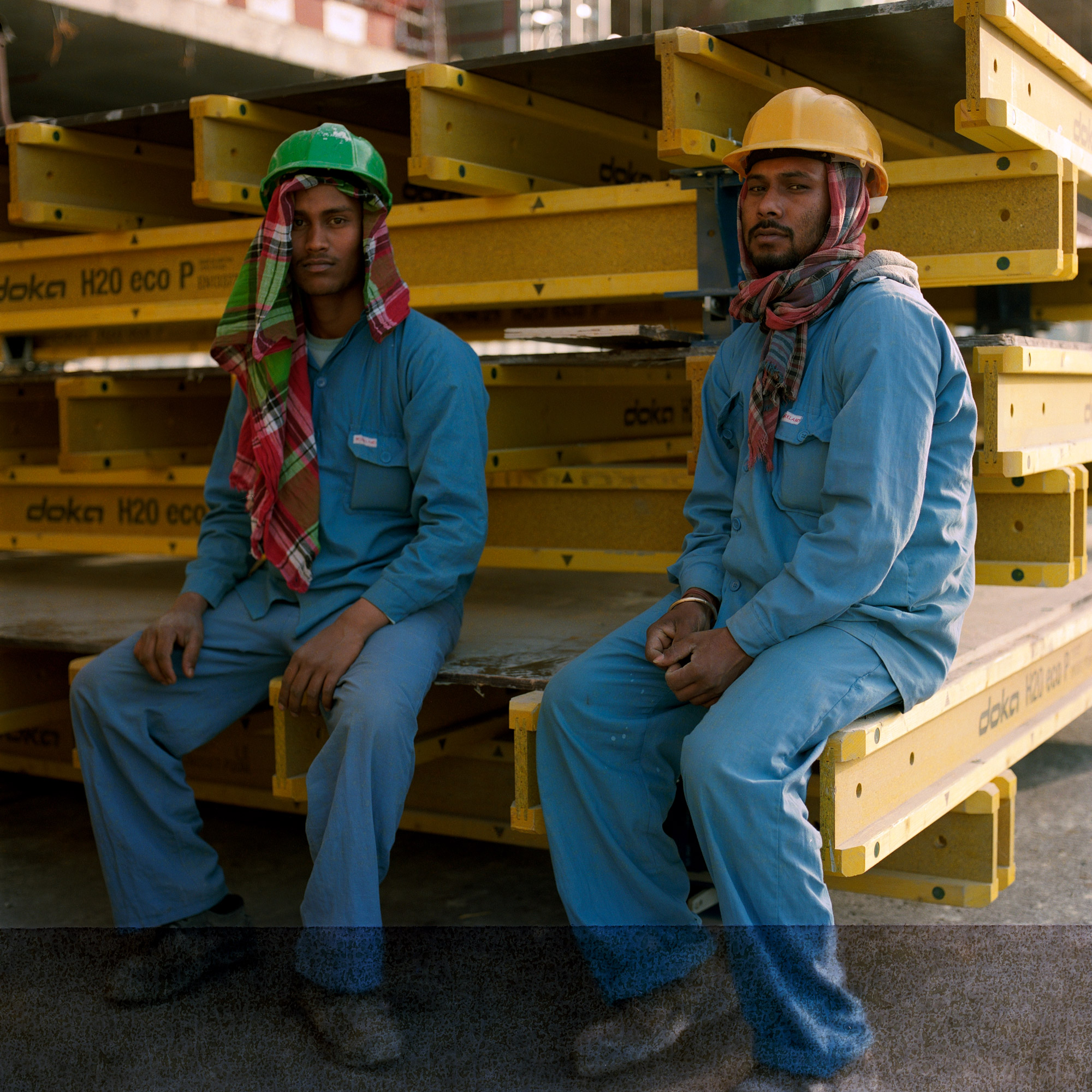 Two Indian construction workers wearing hard hats, workwear, sitting on steal beams in Dubai, Dubai Labourers