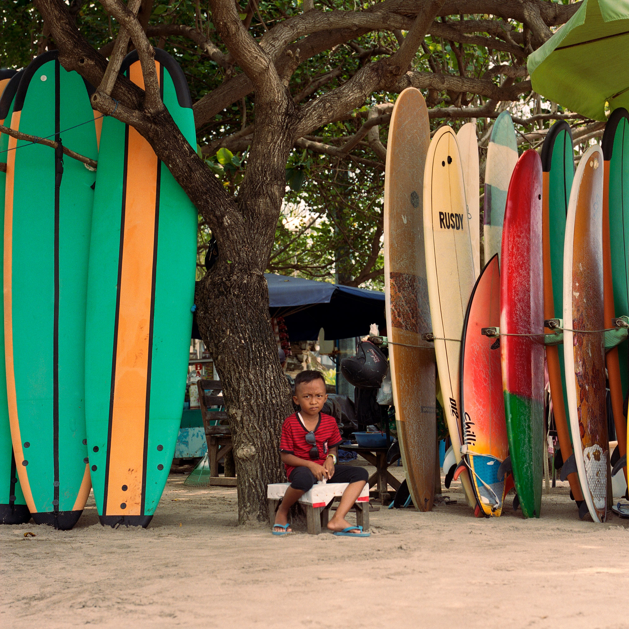 Young Boy Sat At Fathers Beach Surf Shop, Kuta Bali, Eastern Travels, Photography By Ioannis Koussertari