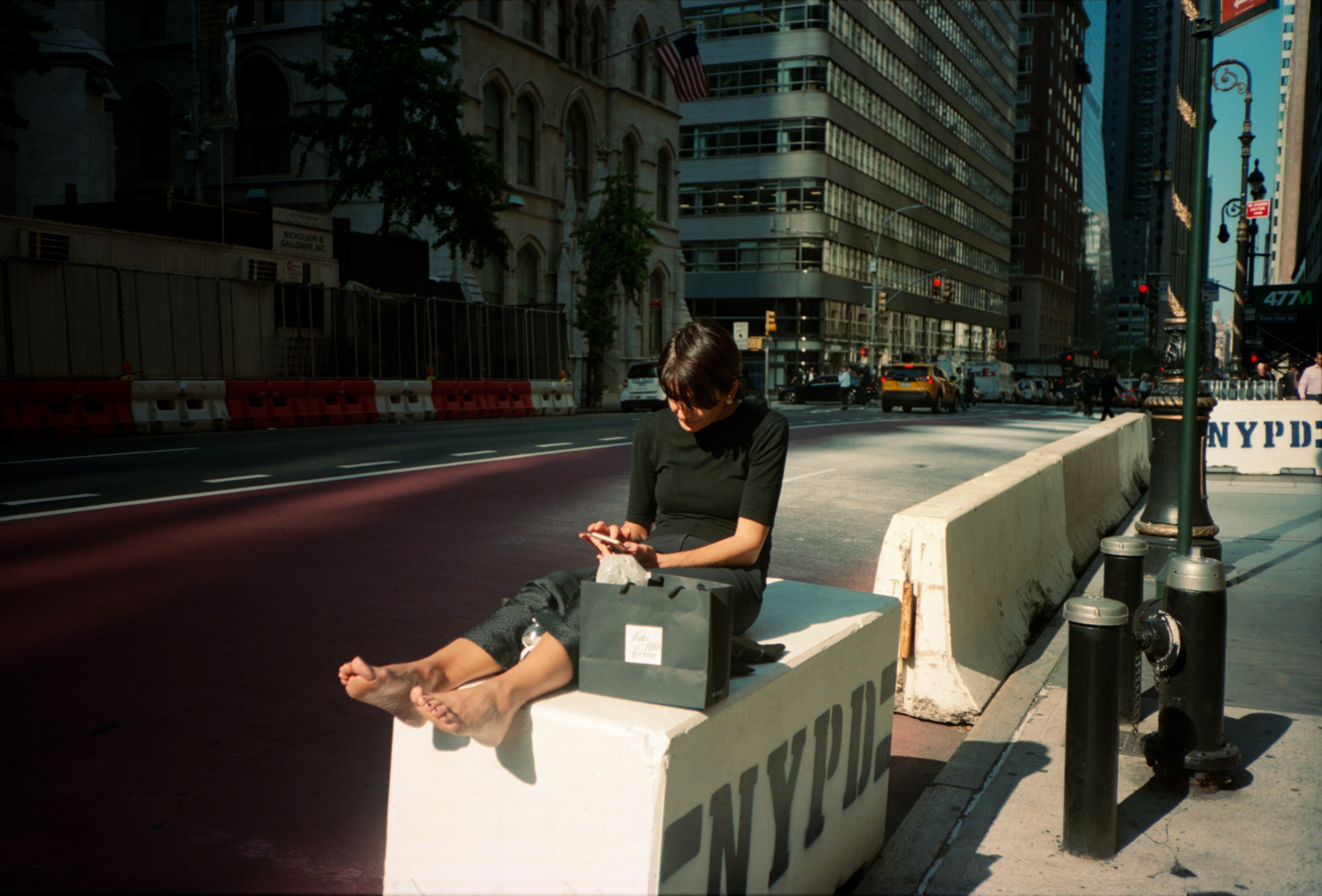 Taking a Break, sitting on an NYPD barricade,  Madison Avenue, Lonely New York, Photography By Ioannis Koussertari.
