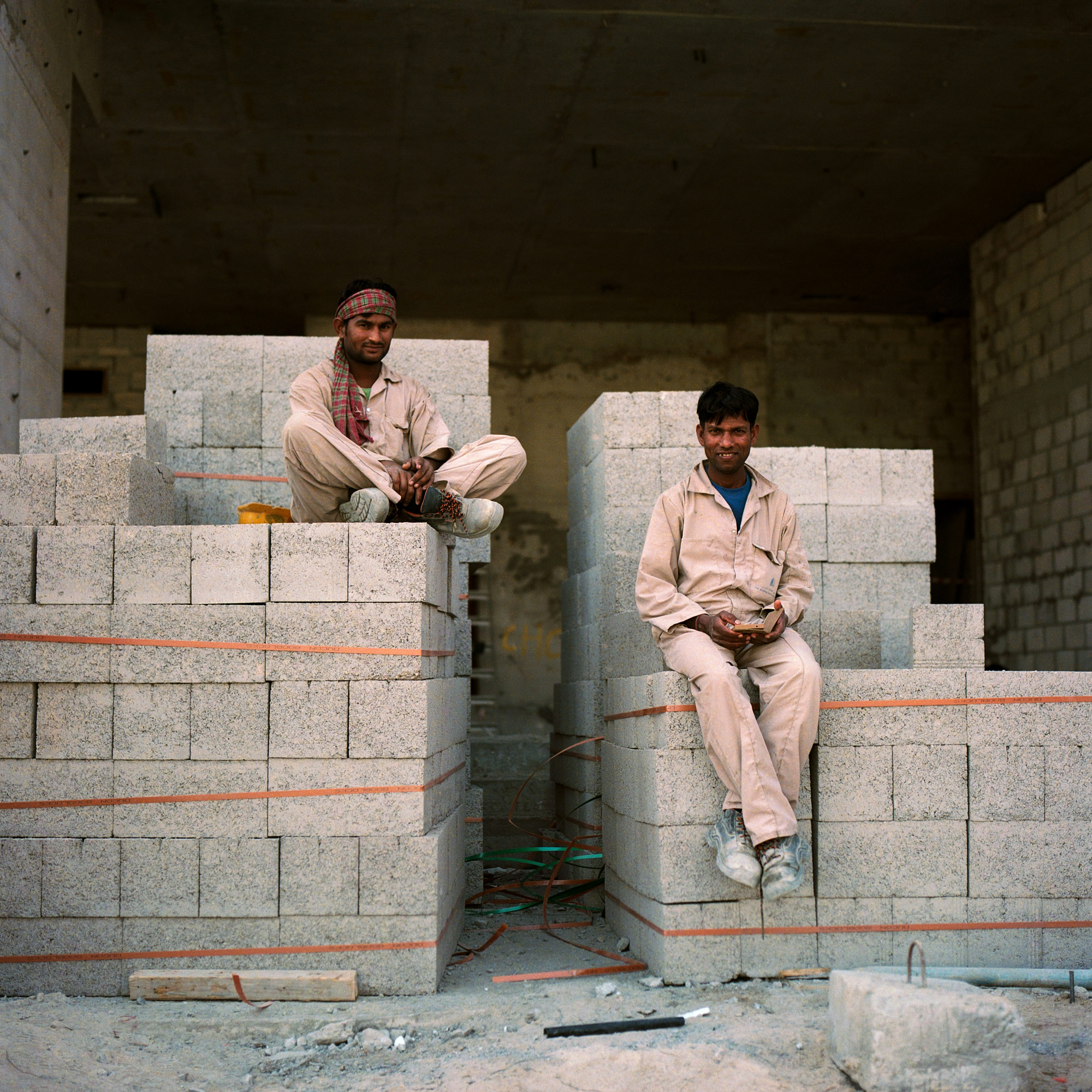 Two Indian construction workers sitting on a pile of breeze concrete building block on site in Dubai, Dubai Labourers